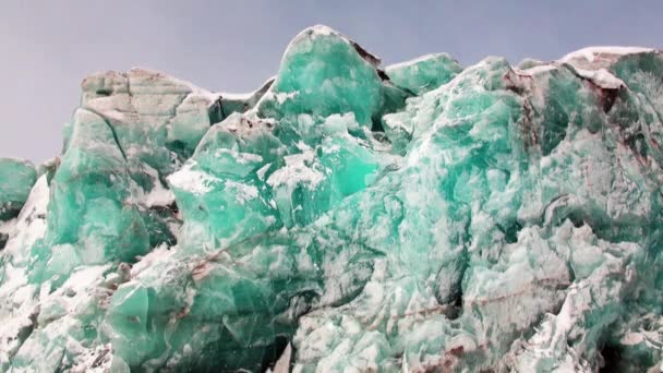 Turquoise color glacier on background of snow in Arctic.