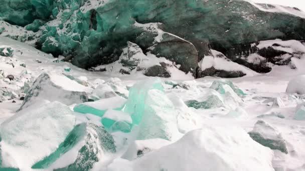 Ledovec krásné jedinečné tyrkysové barvy na pozadí sněhu v Arktidě.