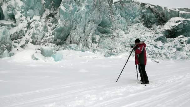 Muž fotograf na krásné jedinečné tyrkysové ledovec v Arktidě.