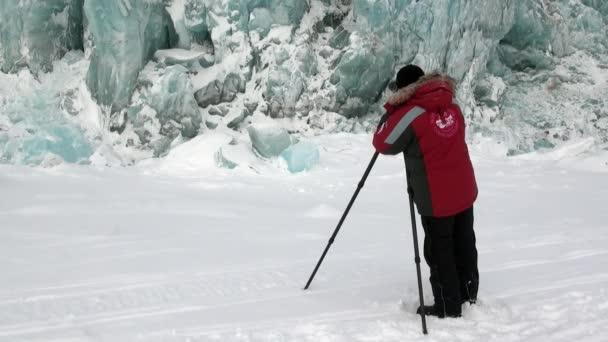 Man photographer on beautiful unique turquoise glacier in Arctic.