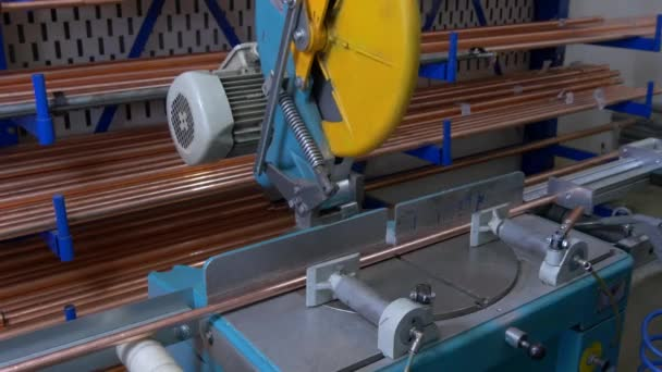 Cutting copper pipes metal with circular saw on automated machine by robot.