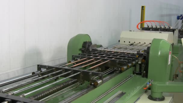 Bending of metal tubes on industrial CNC machine in factory.