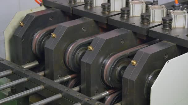 Bending of metal tubes on industrial CNC machine in factory.