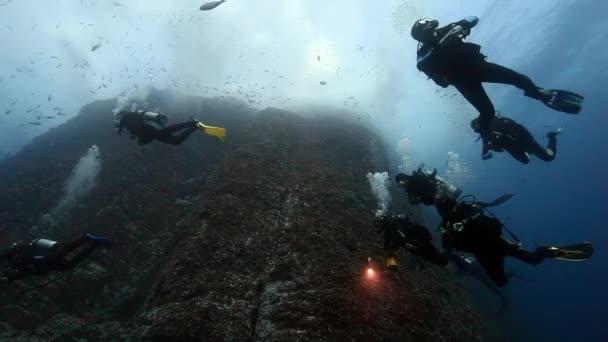 Divers near drop off reef mountain underwater in Pacific ocean.
