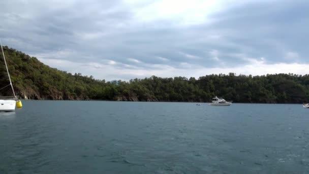 Mavi denizin arka planında beyaz yatlar ve gökyüzünde bulutlar.