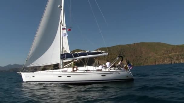 People sail on white yacht on background of mountain coast in Turkey.