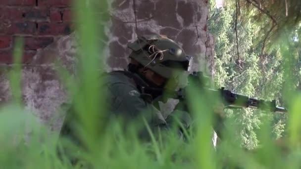 Männer in Militäruniformen mit Waffen vor zerstörtem Haus.