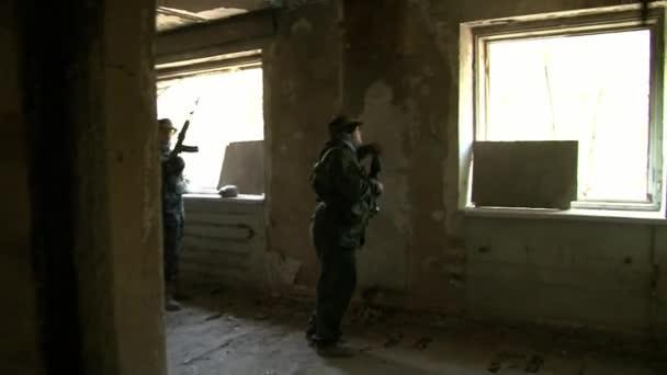 Spieler von airsoft ist in Position in einem zerstörten Haus.