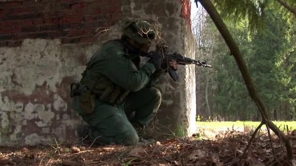 Mann in Militäruniformen mit Waffen vor zerstörtem Haus.