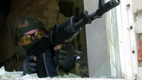 Soldier in military uniform with guns is firing from window of ruined house.