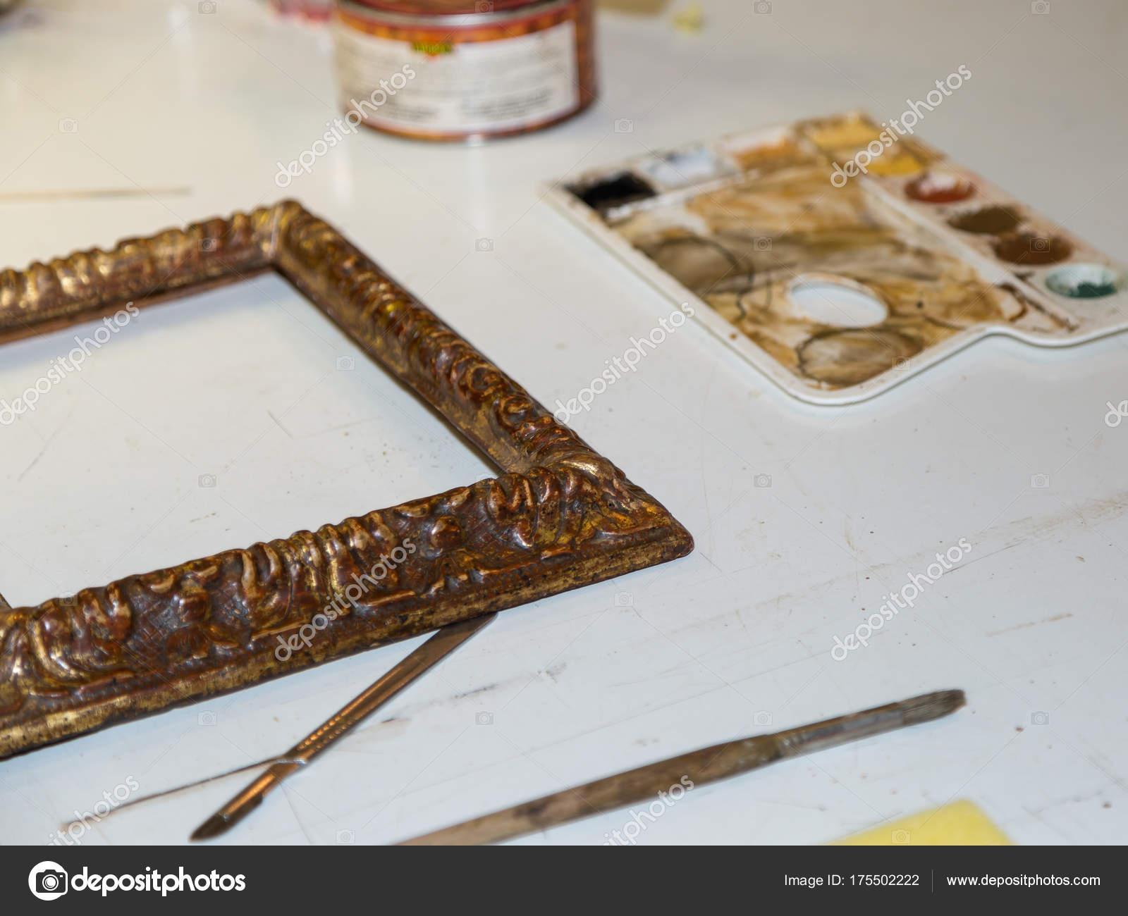Arte paleta, pinceles y marco dorado de madera dentro de tienda de ...