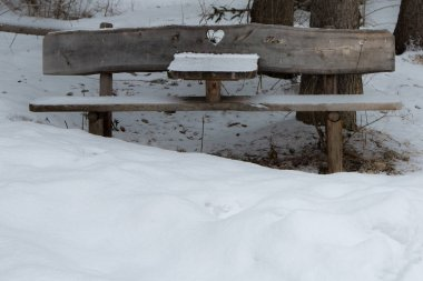 Wooden Bench with Heart Carved in wood Among Fresh Snow in Italian Dolomites Mountains.