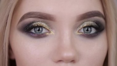 The girl opens her eyes. Girl with beautiful evening make-up,