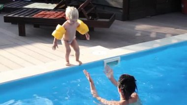 Little boy jumping into the pool with yellow armlets,