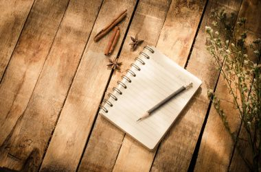 Notebooks, pencils, Equipment on the wooden floor with the morning sun shining faintly.