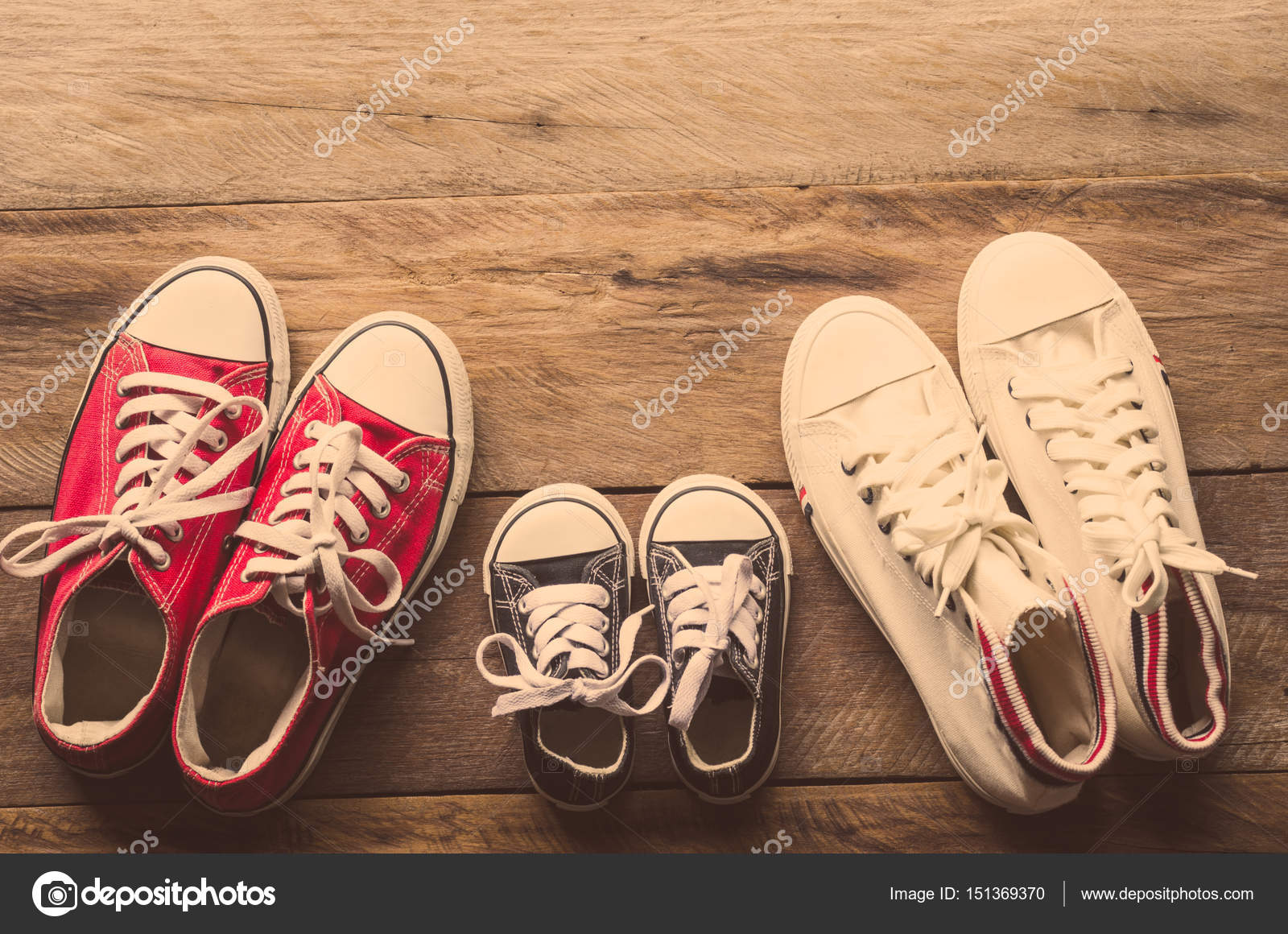 Tres pares de zapatos se ponen en el piso de madera de la