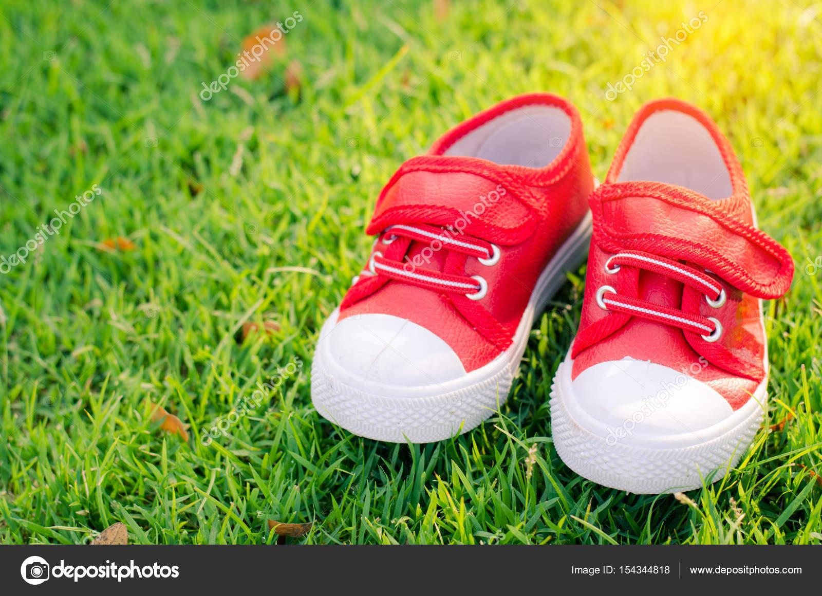 Rote Schuhe Fur Kinder Am Grunen Rasen Boden Stockfoto