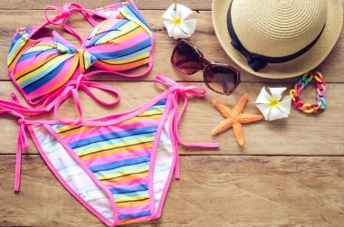 Beauty colorful bikini and accessories on wooden floor for trip