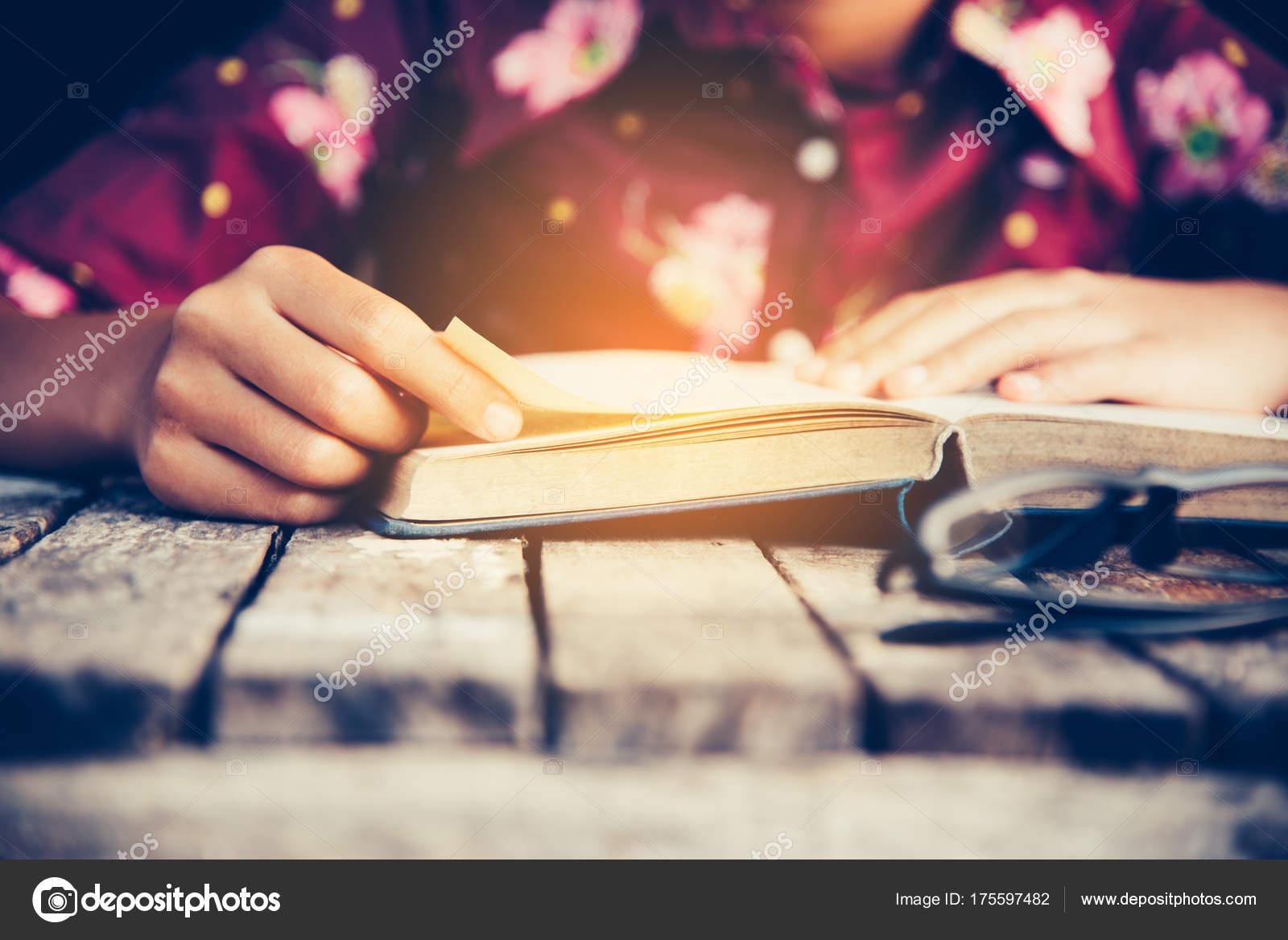 Libro aperto di messa a fuoco a mano per la lettura sulla tavola
