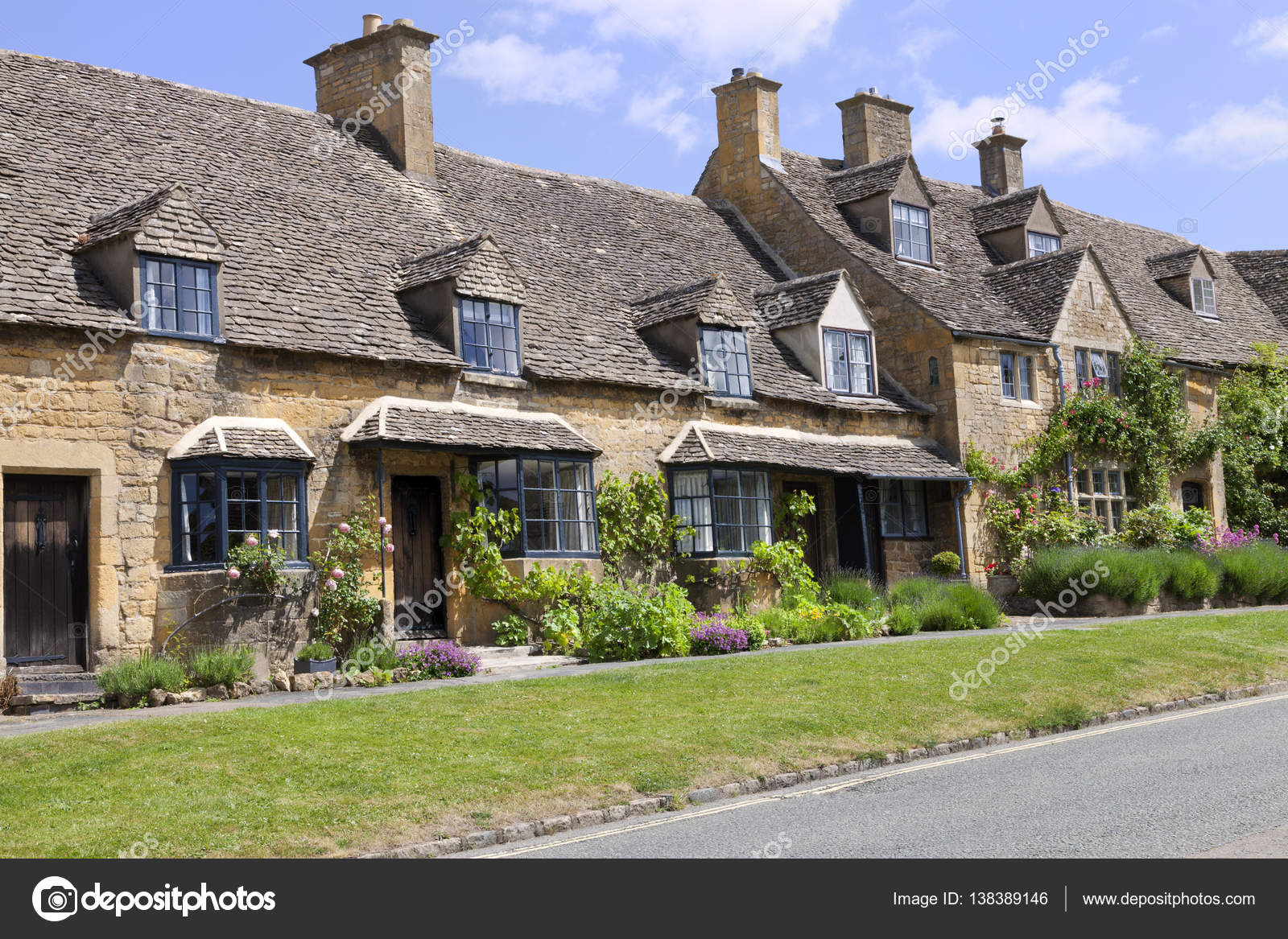 Cotswolds Village Road With Rows Of Old Traditional English Honey Golden Brown Stoned Cottages Colorful Flowering Front Gardens On A Summer Sunny Day
