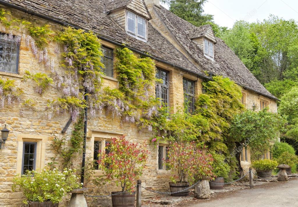 Traditionella, gamla, sten engelska hus med blommande blåregn klättring framvägg ...