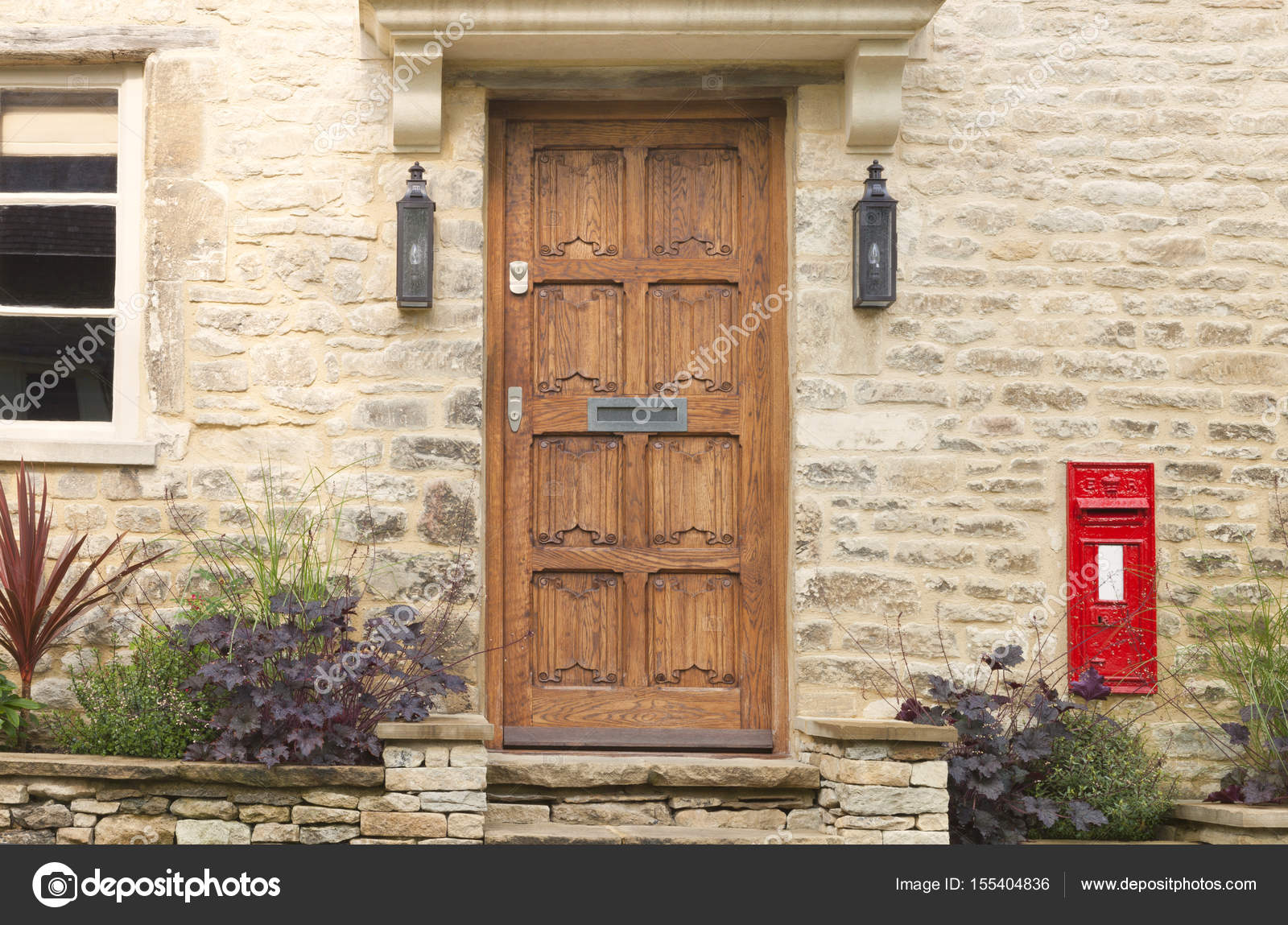 Brown Wooden Doors In An Old Traditional English Golden Stone Cottage With  A Red Post Box In The Wall And Plants In A Small Front Garden .
