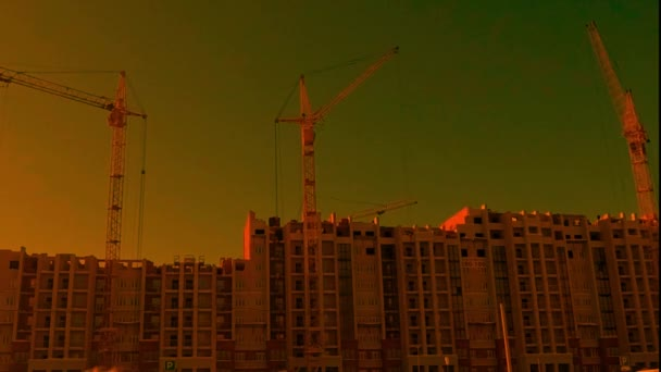 the original image with distorted color reproduction in warm colors. the movement of cranes in the construction of a residential house