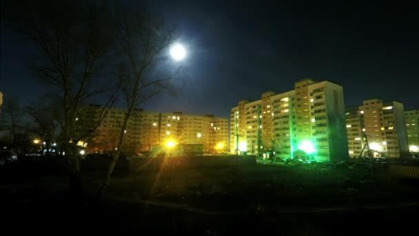 Noční časová osa ve městě, výhled z okna, velký měsíc