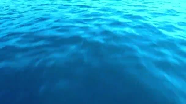 Rychlý pohyb kamery vpřed podél vody textury moře s modrým odstínem bez vln a tryskající z tělesa člunu. Ve vodě odrážejí paprsky slunce při západu slunce