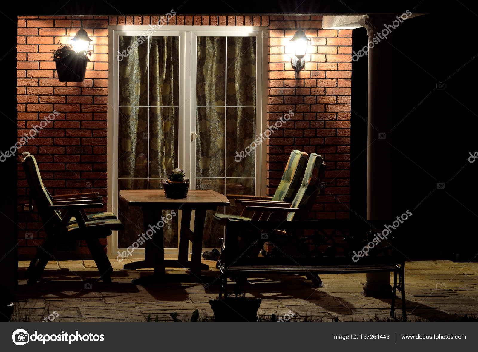 Terraza (patio) de la casa moderna con muebles de jardín en la noche ...