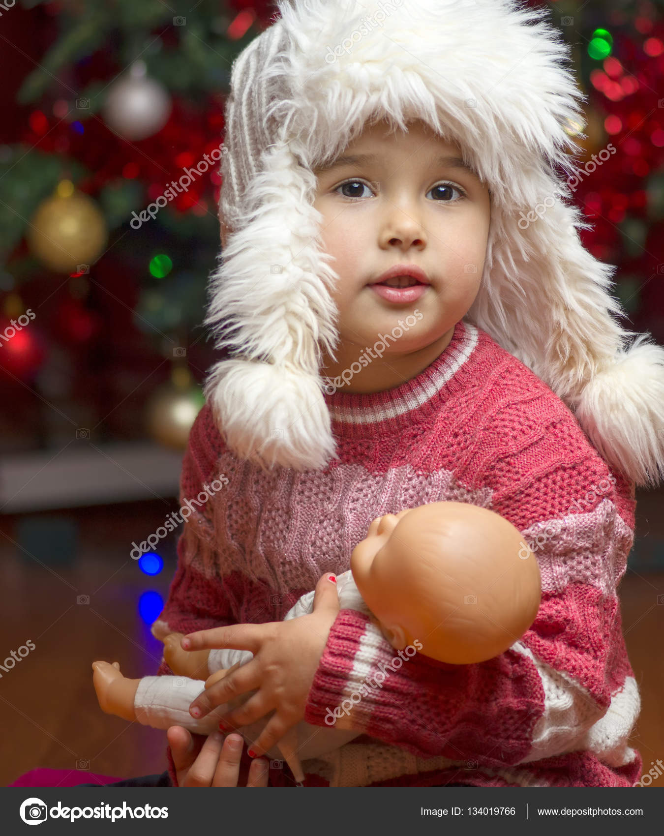 Girl with a favorite toy doll with Christmas lights background