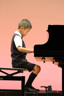 Japanese boy playing a piano (first grade at elementary school)