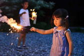 Fotografia Japanese brother and sister doing handheld fireworks (7 years old boy and 2 years old girl)