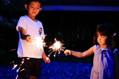 Japanese brother and sister doing handheld fireworks (7 years old boy and 2 years old girl)