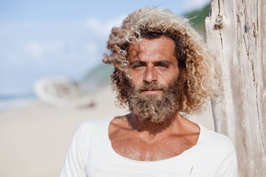 Robinson Crusoe. Portrait of curly-bearded man on the beah with a ship wreckage on the background.