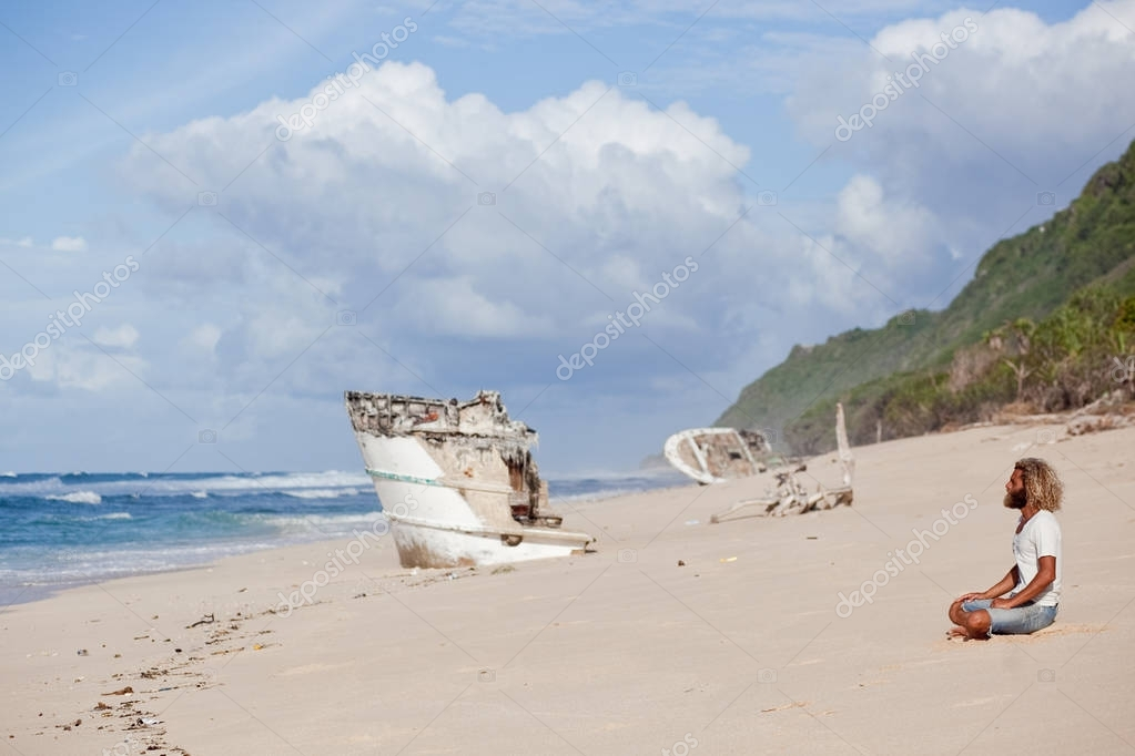 Robinson Crusoe. curly-bearded man is sitting on the beach with a ship's wreckage on the backgraund.