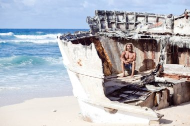 Robinson Crusoe. Curly-bearded man is sitting on the wreck of the ship on the beach