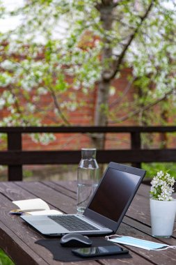 distant work or study from home during the coronavirus pandemic. Medical mask, laptop, mouse, notepad, mobile phone on a brown wooden table. Blooming tree. Spring time