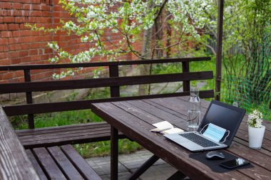remote work or distant study from home during the coronavirus pandemic. Medical mask, laptop, mouse, notepad, mobile phone on a brown wooden table in garden. Blooming tree. Spring