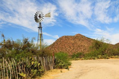 Windmill, mountain and butterfly garden along a fence on the La Posta Quemada Ranch with copy space in ColossWindmill and Butterfly Garden on La Posta Quemada Ranch in Colossal Cave Mountain Paral Cave Mountain Park in Vail, Arizona, USA near Tucson.