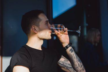 tattooed man drinking wine