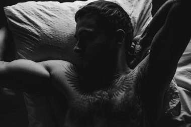 Tattooed man in bed