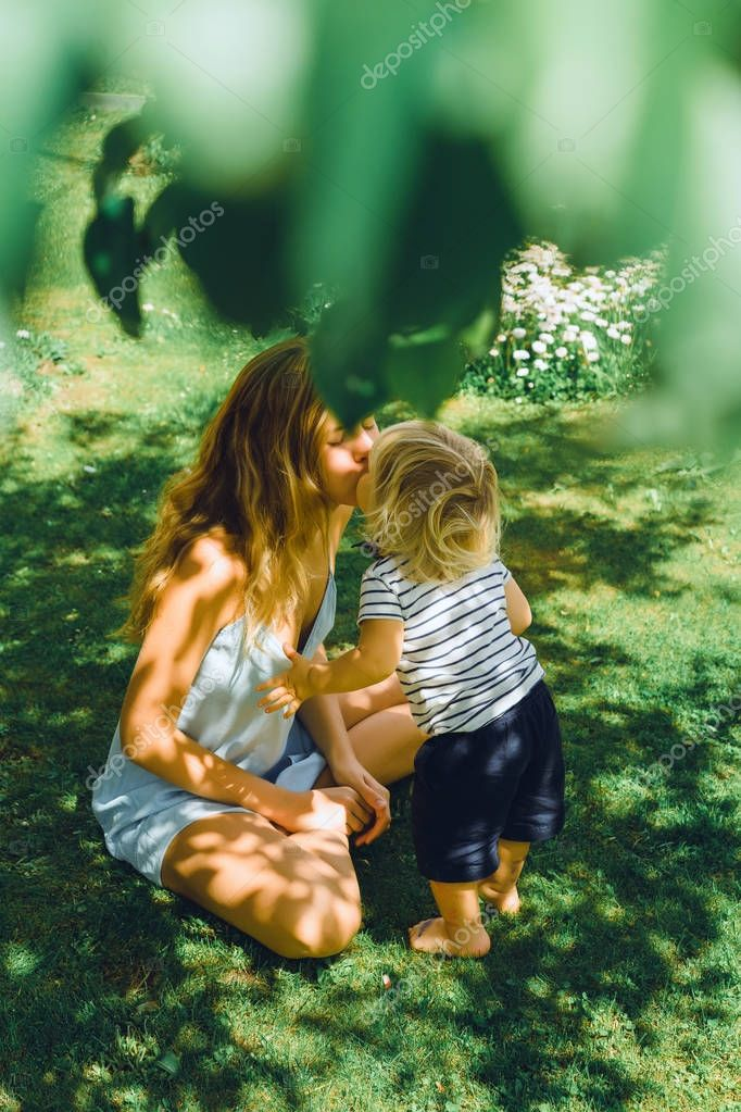 young mother kissing cute blonde boy on green grass outdoor at summer