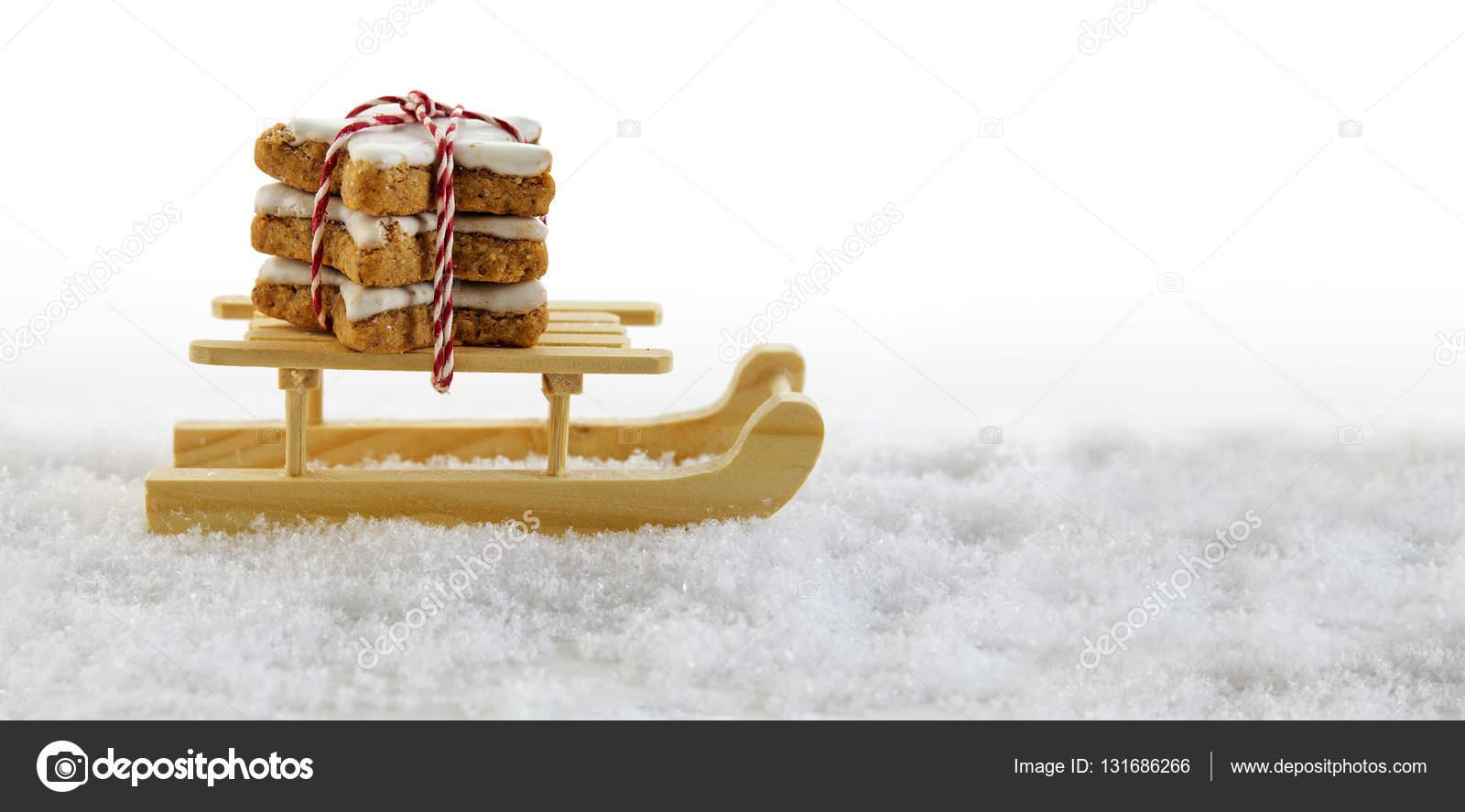 Weihnachtsgebäck Zimtsterne.Holzschlitten Im Schnee Mit Zimtsterne Traditionelles