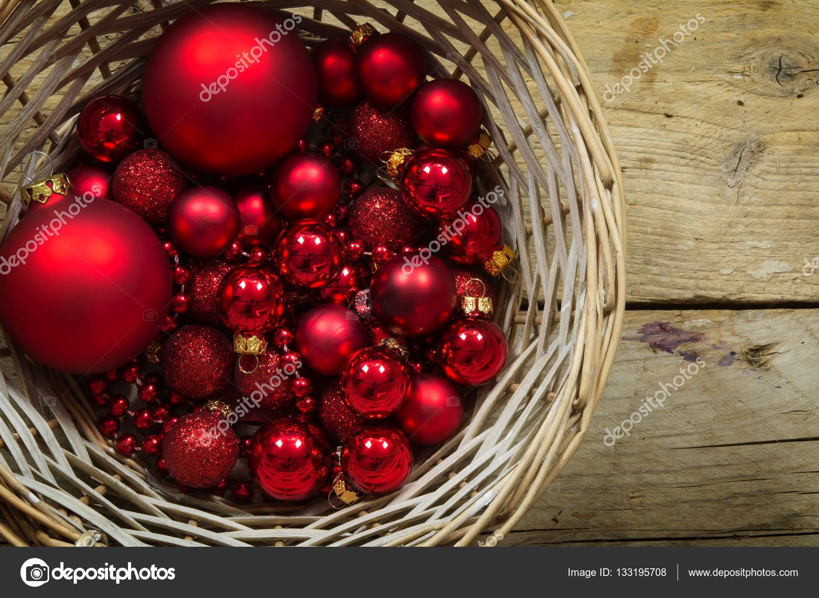 Red christmas balls and baubles in a basket on a rustic wooden