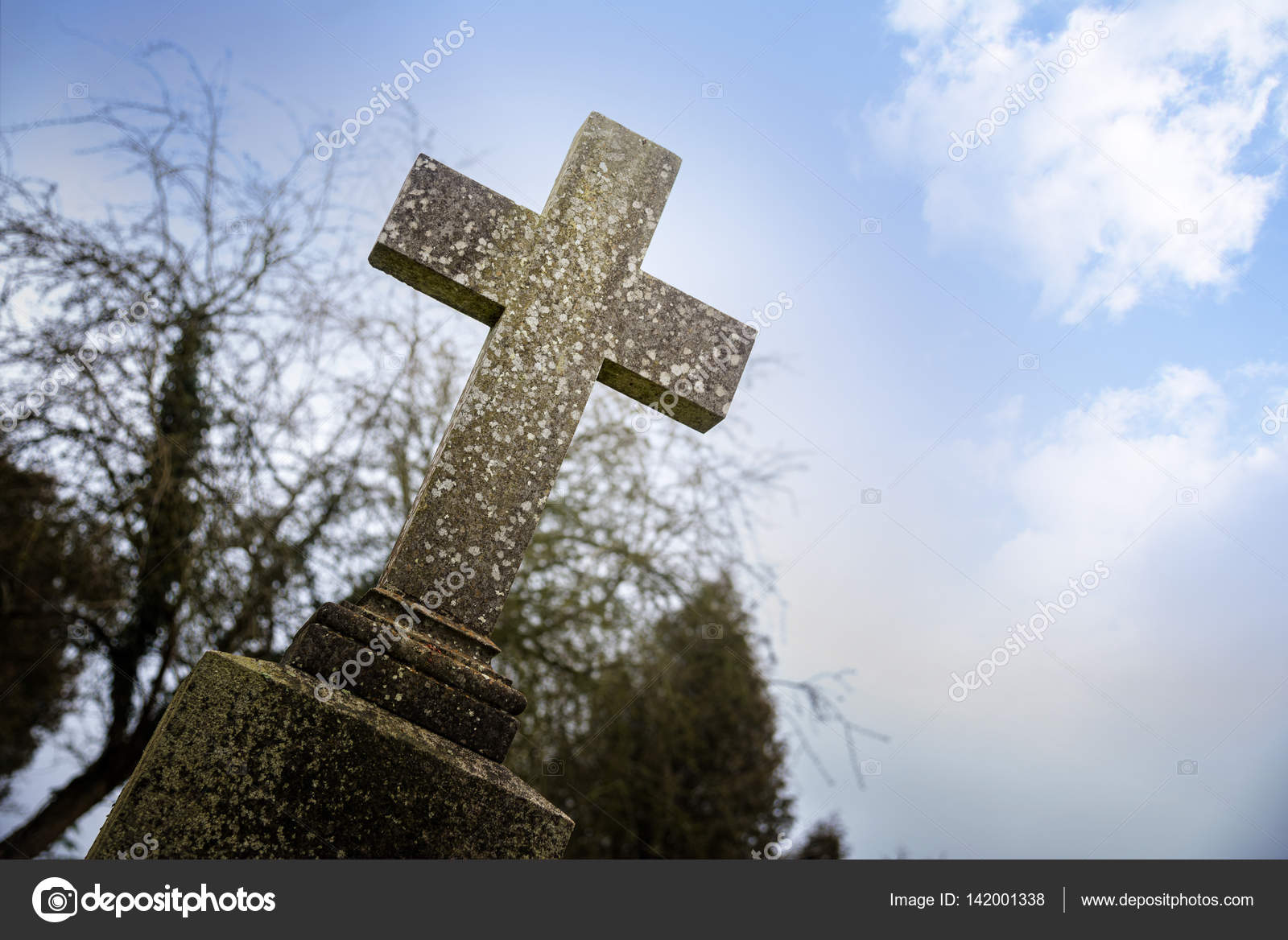 Weathered stone cross or gravestone against the blue sky memorial weathered stone cross or gravestone against the blue sky memorial day concept for war dead or religious christian symbol for holiday like good friday biocorpaavc Images