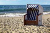 Sedia di cesto tipica della spiaggia in sabbia sul mare blu in una giornata di vacanza al sole