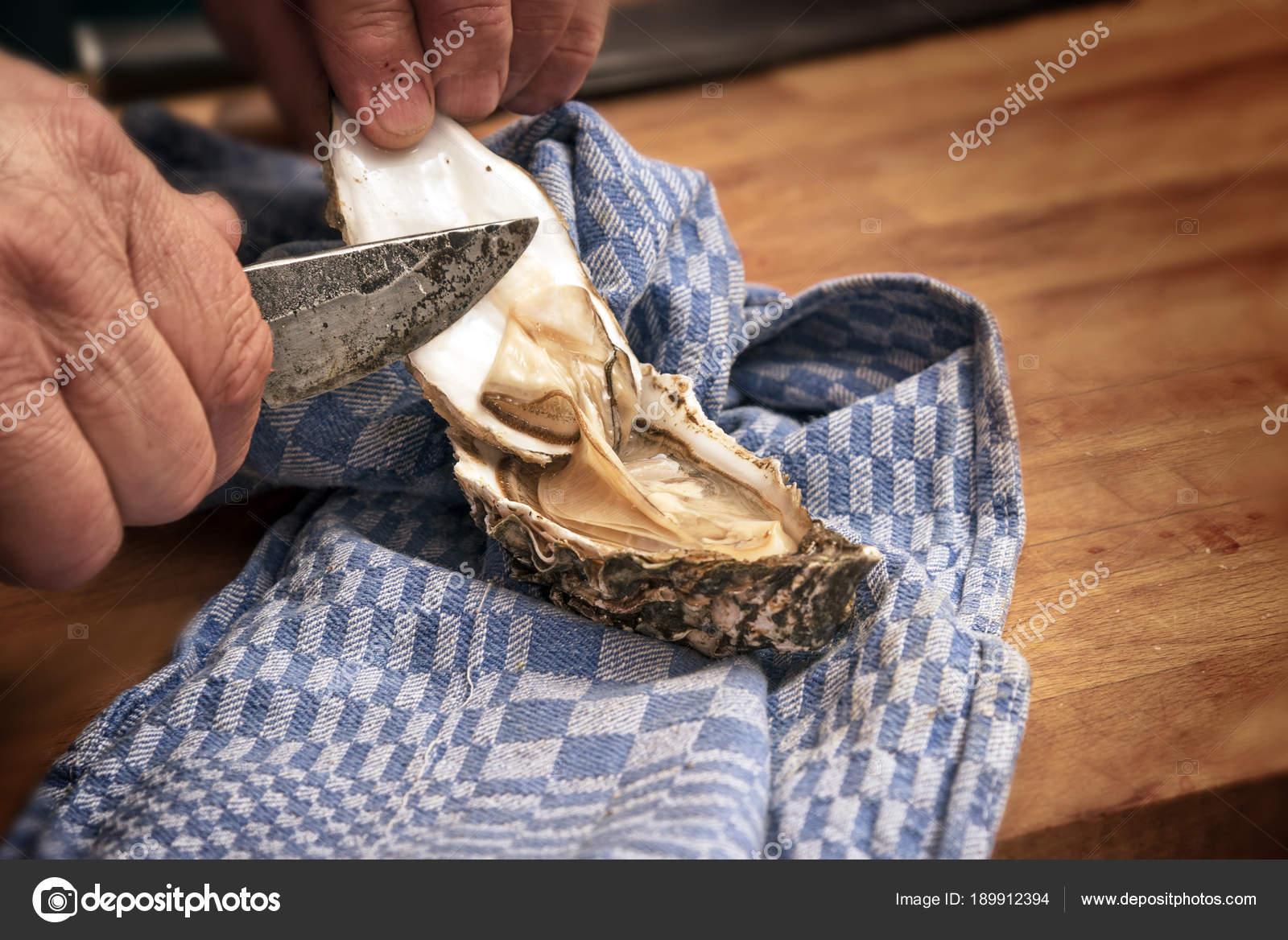 manos de los hombres valvas de una ostra fresca con un cuchillo ...