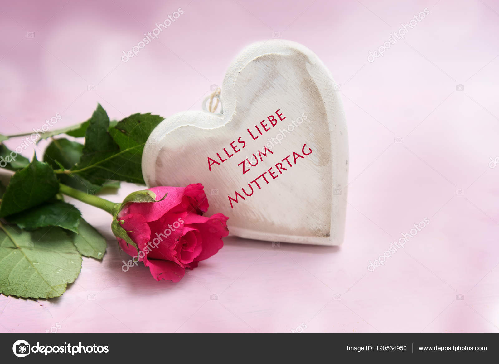 heart of wood and a rose on a pink background, german text Alles ...