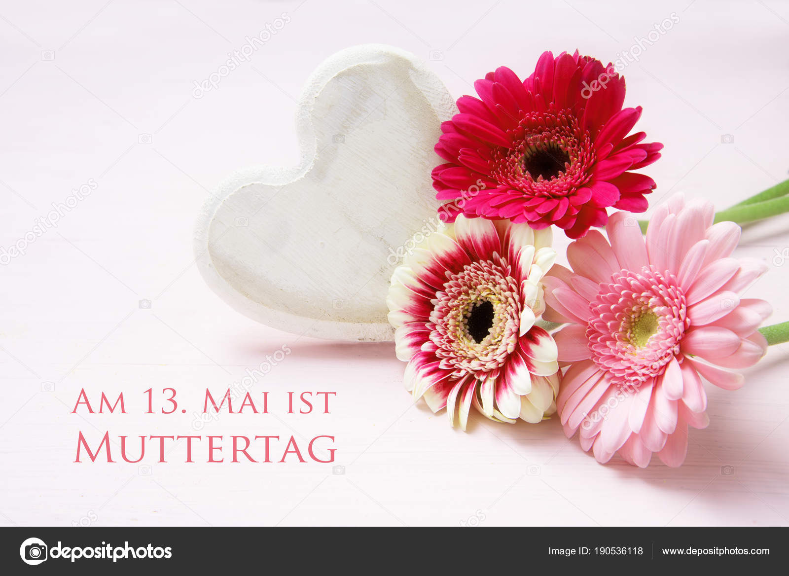 Pink flowers and a white painted wooden heart on a pastel colored pink flowers and a white painted wooden heart on a pastel colored background german text am 13 mai ist muttertag meaning may 13 is mothers day mightylinksfo